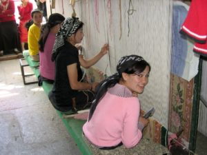 Uyghur women in the city of Hotan, East Turkistan making carpets in a carpet factory.